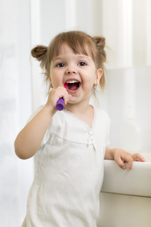 Cute little child girl brushing teeth in bathroom Stock Photo