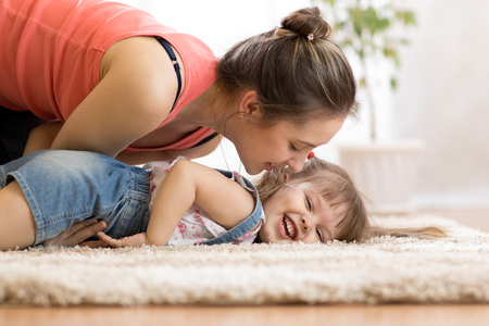 love and family concept - happy mom and child daughter having fun pastime at home Stock Photo