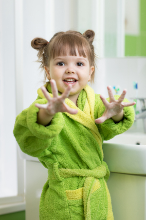 Cheerful kid girl washing hands and showing soapy palms