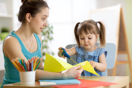 Teacher helps child to cut colored paper Stock Photo