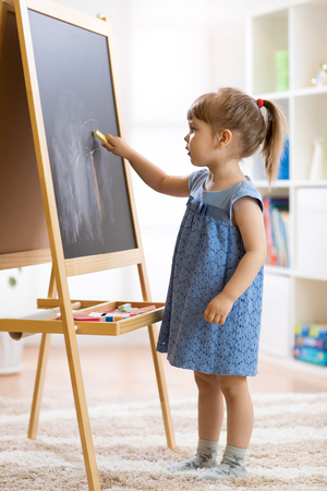 Little girl draws with chalk on the blackboard