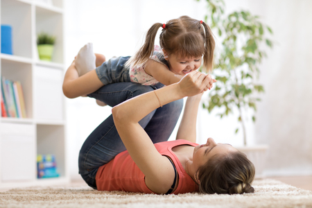 Love and family people concept - happy mom and child daughter having a fun at home Stock Photo
