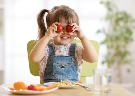 Child girl having fun with food vegetables at nursery room Stock Photo