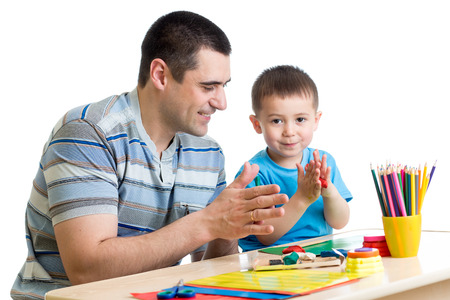 Father and his child have a fun pastime with colorful play clay toys