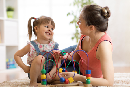 Kid girl plays with educational toy in nursery at home. Happy mother looking at her smart daughter.