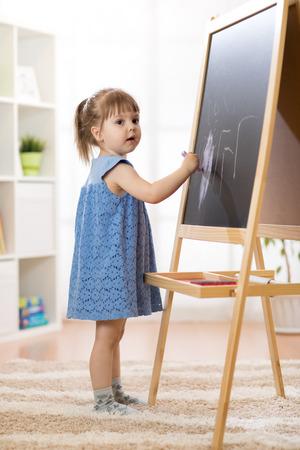 Little kid girl draws with chalk on the blackboard