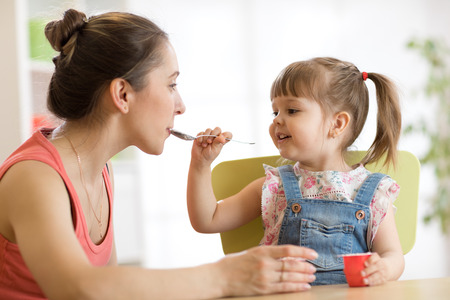 playful baby girl spoon feeding her mother Stock Photo