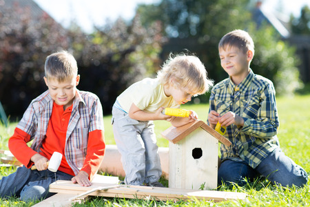 Happy kids boys brothers tinkering outdoors at sunny day Stock Photo