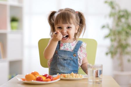 Smiling toddler girl eats at home