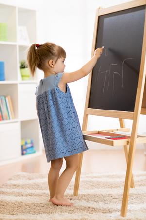 Childgirl draws with chalk on the blackboard