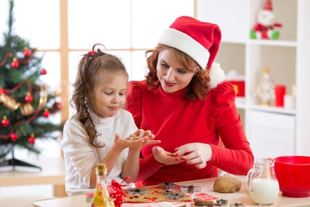 Adorable little girl and mother baking Christmas cookies