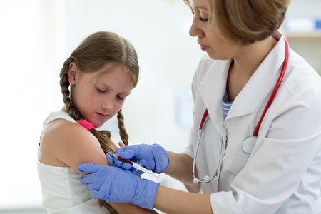 Doctor give injection to girls arm