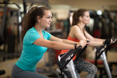 Attractive young women in sports clothing exercising on gym bicycles Stock Photo