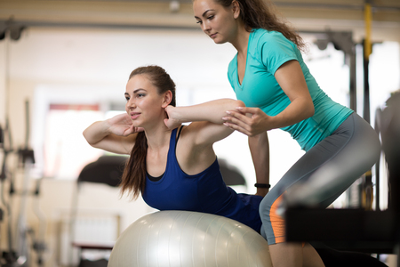 Fitness trainer helping young girl doing back exercises in gym Stock Photo