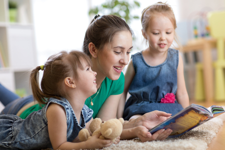 Young mom reads story to her little daughters. Family relaxing on floor