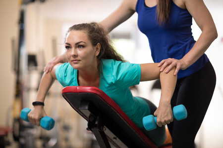 Fitness trainer helping young woman doing exercises in gym Stock Photo