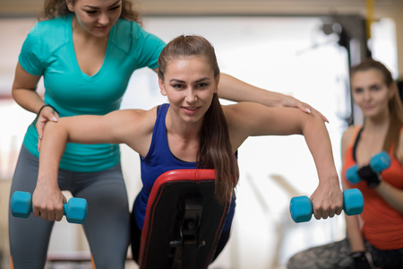 Fitness trainer helping young woman doing exercises on bench. People doing sport in gym.