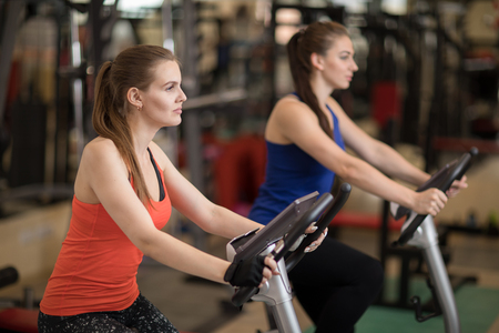 Fitness practice, two young women cycling in sports club, doing cardio exercises