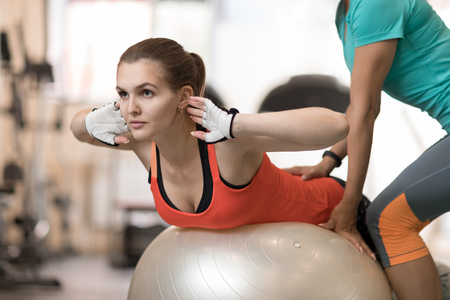 Fitness trainer helping young woman doing back exercises in gym Stock Photo