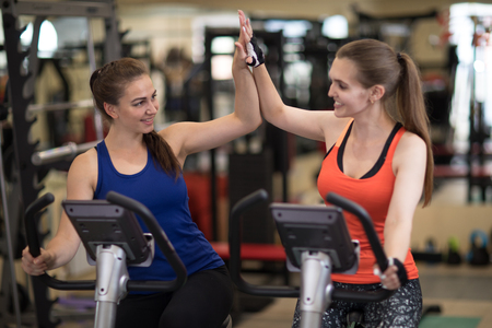 Two cheerful girls exercising together in gym sport club Stock Photo