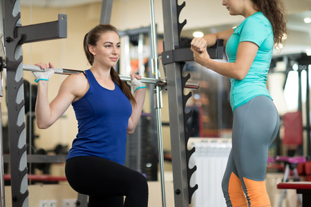 Pretty girl using barbell in gym. Trainer keep watch over her