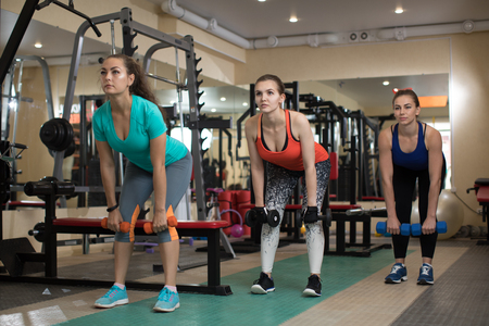 Three pretty fitness active girls doing exercises with kettlebells in gym.
