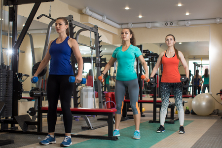 Three young fitness active girls doing exercises with kettlebells in gym.