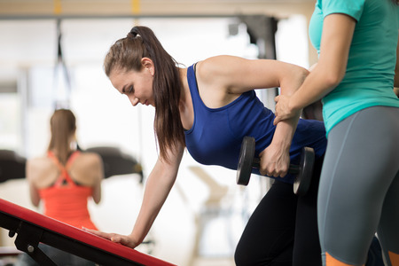 Fitness trainer helping young girl doing exercises in gym