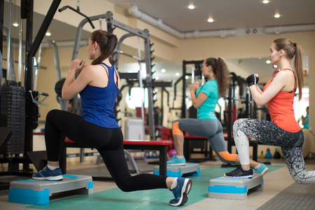Group of young women flexing muscles in gym. Concept of sport, fitness, health and lifestyle. Stock Photo