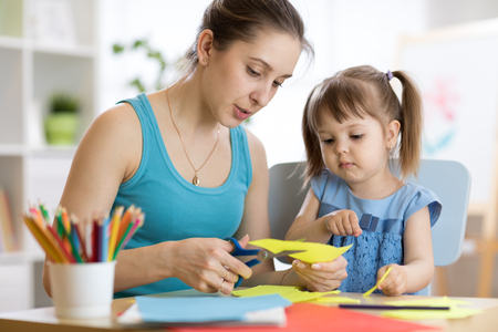 Teacher helping child to work colored paper