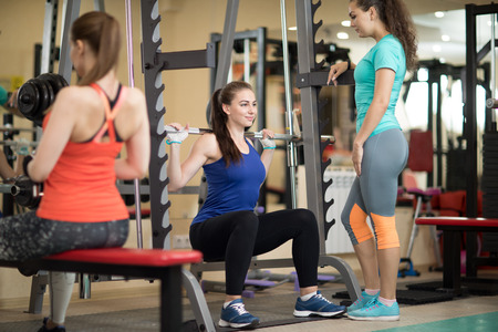 Pretty young woman using barbell in gym. Trainer keep watch over her Stock Photo