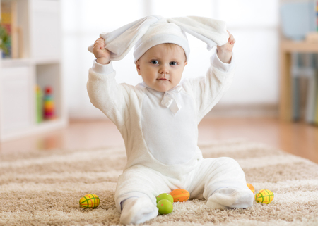 Funny baby girl in rabbit costume sitying on rug in nursery