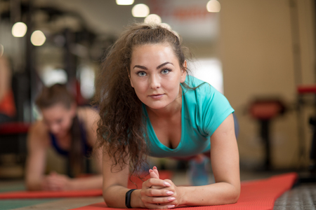 Young sporty beautiful girl training on mats in gym
