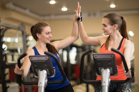 Two cheerful young women exercising together in gym sport club Stock Photo