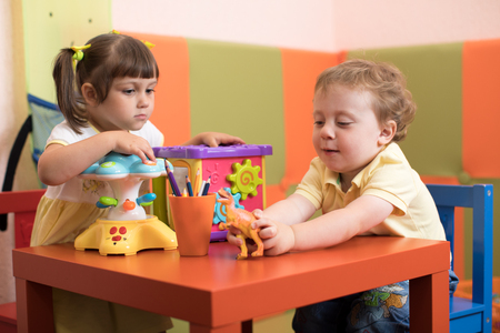 Children girl and boy play in kids daycare centre