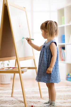 Child girl draws on a white board with a felt-tip pen.