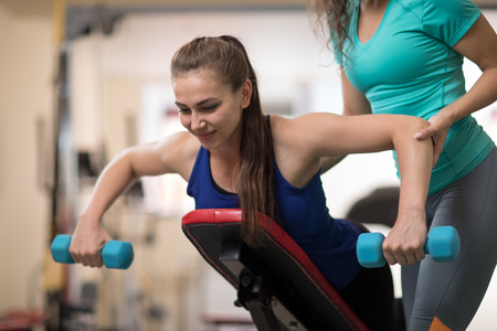 Personal trainer helping young woman with weight training equipment in gym