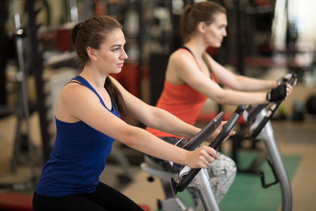 Attractive young girls in sports clothing exercising on gym bicycles