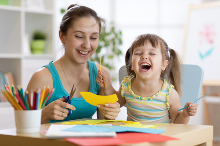 mother with little daughter fun cut scissors colored paper
