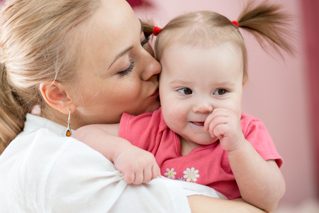 Portrait of a joyful mother kissing her baby daughter at home Stock Photo