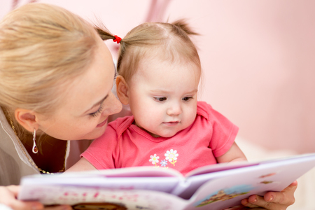 Happy mom reading book to baby girl indoors