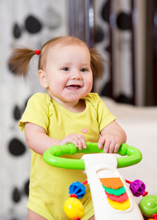 Baby girl smiling while standing in a walker Stock Photo