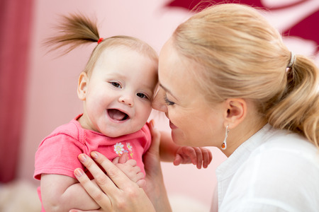 Portrait of a joyful mother with her baby daughter at home Stock Photo