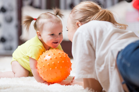 Woman with her baby playing with a ball, while they are lying on plush carpet in the living room Stock Photo