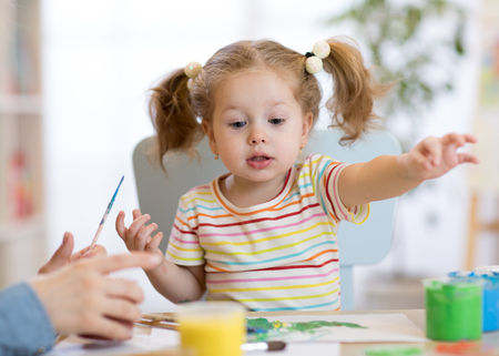 Cute little toddler girl in striped shirt and pony tails paints in the art class Stock Photo