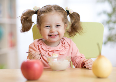 Baby girl eating fruits at home Stock Photo