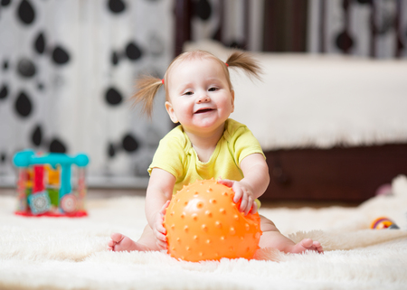 Childhood and people concept - happy baby playing with ball on floor at home Stock Photo