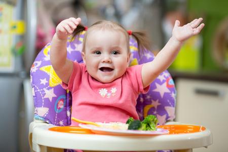 Baby eats pasta sitting in highchair in kitchen