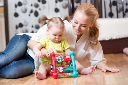 Mother and daughter playing together with colorful logical toy on the floor of a bedroom at home