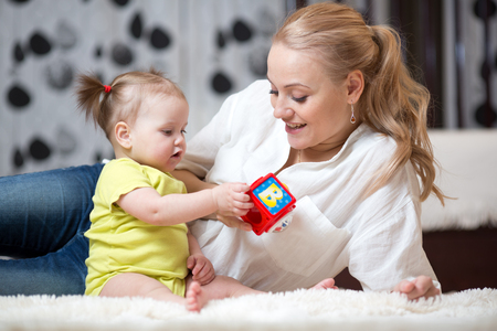 Mother and baby girl playing with developmental toys in living room